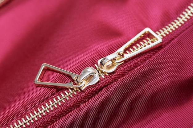 Nahaufnahme des goldenen reißverschlusses. geknöpfter metallreißverschluss an rucksack oder kleidung.