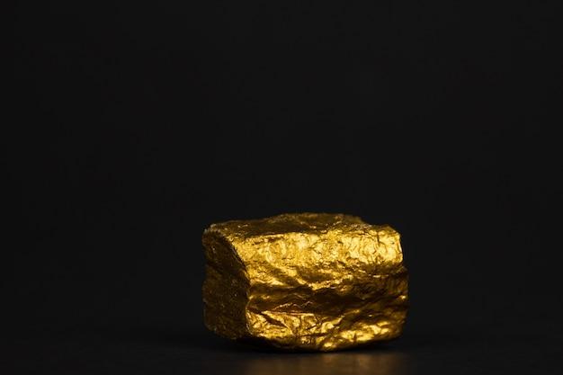 Nahaufnahme des goldnuggets oder des golderzes auf schwarzem hintergrund