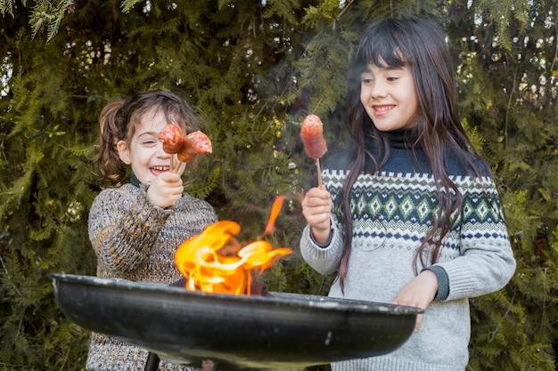 Nahaufnahme des grills vor zwei glücklichen mädchen, die würste halten