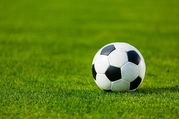 Nahaufnahme des grünen fußballplatzes mit fußball