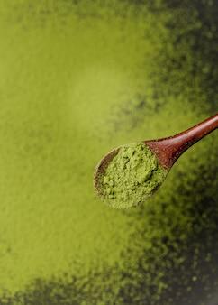 Nahaufnahme des grünen matcha teepulvers auf hölzernem löffel