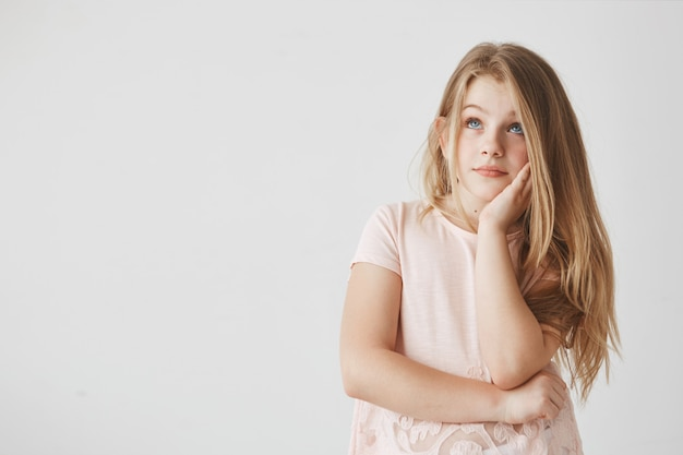 Nahaufnahme des gutaussehenden mädchens mit blonden haaren und blauen augen, die hand auf wange halten, mit verträumtem ausdruck beiseite schauend, über feiertage denkend.