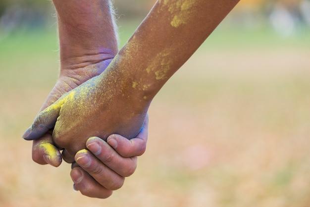 Nahaufnahme des händchenhaltens, während sie in der farbe bedeckt werden