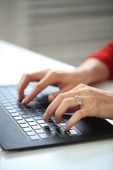 Nahaufnahme des händeschreibens mit computertastatur