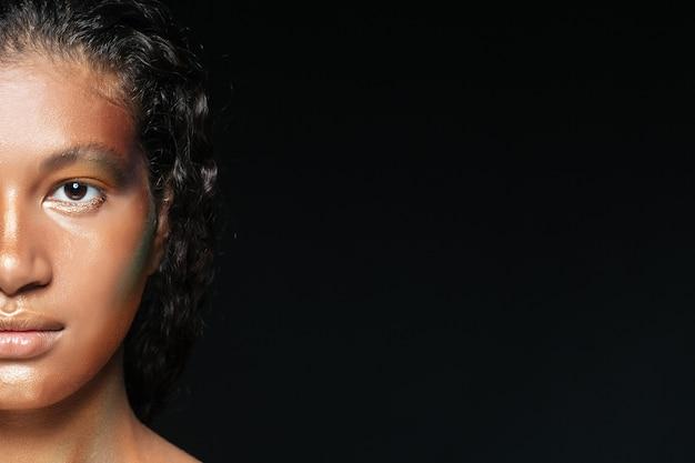 Nahaufnahme des halben gesichts der schönen amerikanischen jungen frau mit glänzendem make-up über schwarz