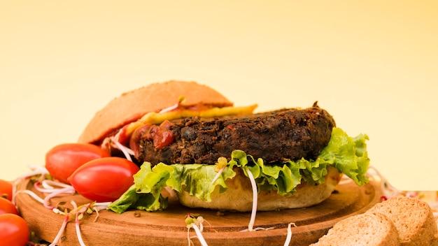 Nahaufnahme des hamburgers mit kopfsalat und tomaten auf hackendem brett über dem gelben hintergrund