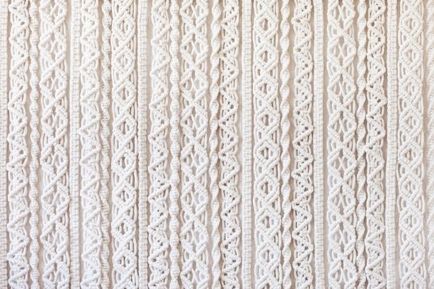 Nahaufnahme des handgemachten makramee-texturmusters. eco-freundliches modernes strick-diy-naturdekorationskonzept im innenraum. flach liegen. handgemachte makramee 100% baumwolle. weibliches hobby.