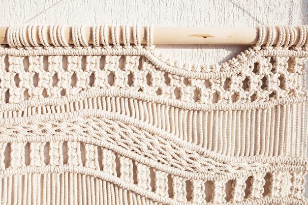 Nahaufnahme des handgemachten makramee-texturmusters. umweltfreundliches modernes stricken diy natürliches dekorationskonzept im innenraum. handgefertigte makramee 100% baumwolle. weibliches hobby.