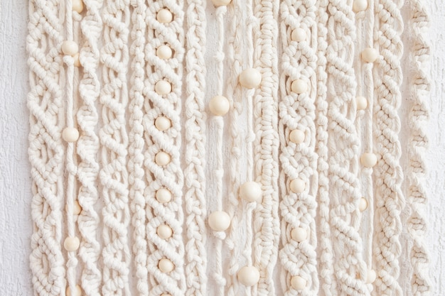 Nahaufnahme des handgemachten makramee-texturmusters. umweltfreundliches modernes stricken. natürliches dekorationskonzept im innenraum.