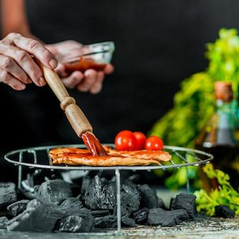 Nahaufnahme des handpinselsoßenbades auf fleisch für das grillen