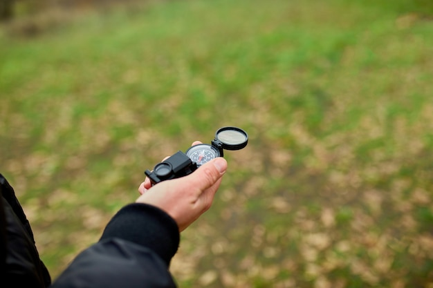 Nahaufnahme des handreisenden mannes mit kompass auf einer wand der natur, reisekonzept, campingausflug, gps, orientierungslauf, navigator