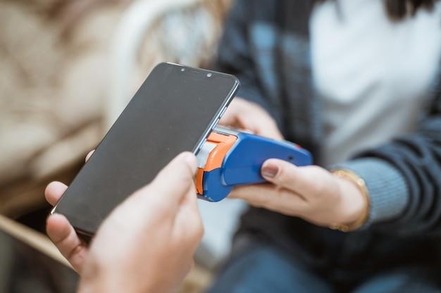 Nahaufnahme des handys in der nähe der elektronischen datenerfassungsmaschine beim einkaufen im geschäft