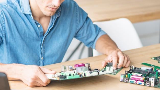 Nahaufnahme des hardwaretechnikers motherboard reparierend