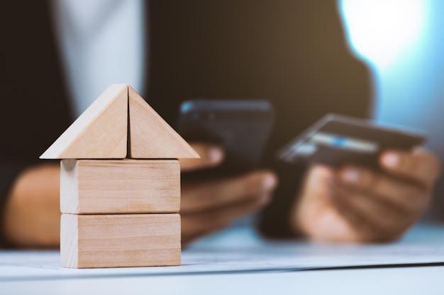 Nahaufnahme des hausarchitekturmodells mit dem wirtschaftler, der kreditkarte hält und mobile verwendet
