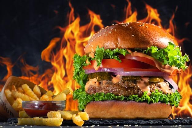 Nahaufnahme des hausgemachten leckeren burgers mit pommes frites und feuerflammen.