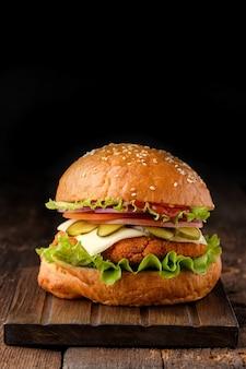 Nahaufnahme des hausgemachten leckeren hamburgers auf holztisch.