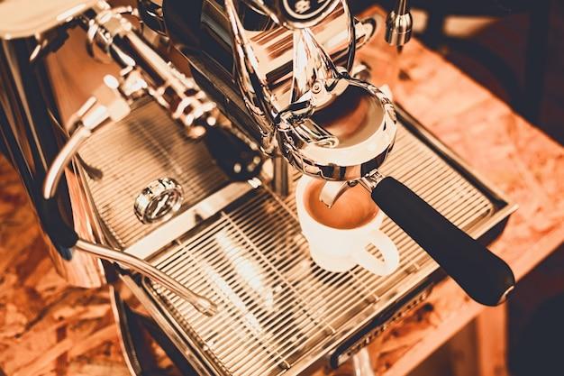 Nahaufnahme des heißen kaffees von der kaffeemaschine. professionelles kaffeebrühen