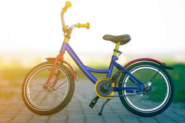 Nahaufnahme des hellen mehrfarbigen blauen, gelben und roten fahrrads des kindes links auf seitenständer in der mitte der leeren gepflasterten straße auf unscharfem hellem bokeh-hintergrund gestützt. konzept des aktiven lebensstils der kinder.