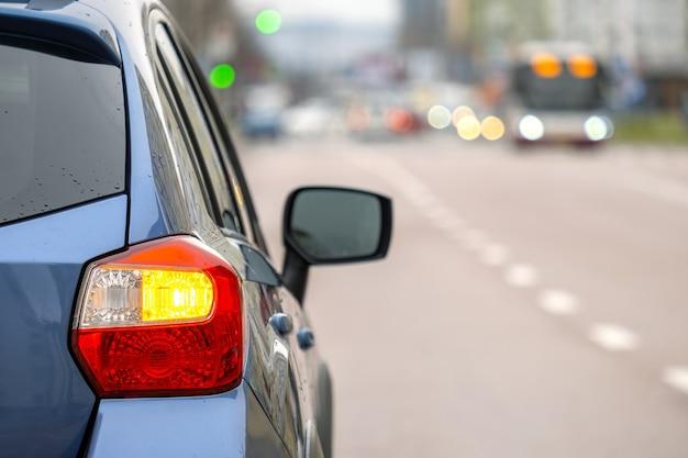 Nahaufnahme des hinteren scheinwerfers des neuen sauberen autos, das auf einer straßenseite der stadt geparkt ist.