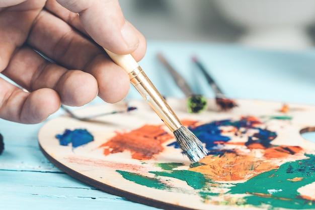 Nahaufnahme des hochbegabten malers, während er sein bild malt.