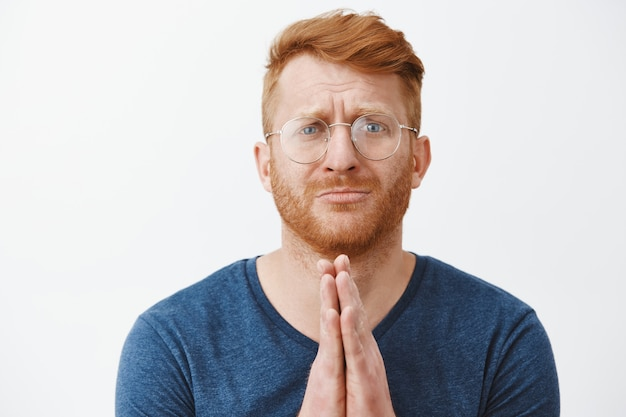 Nahaufnahme des hoffnungsvoll flehenden rothaarigen mannes in der brille brauchen hilfe, die sie bittet