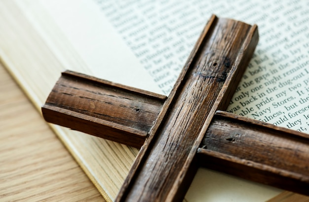 Nahaufnahme des holzkreuzes auf bibelbuch