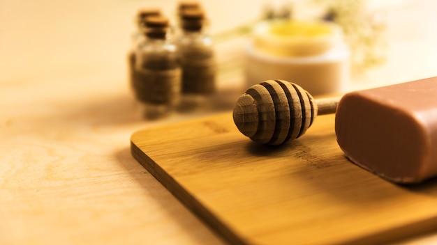Nahaufnahme des honigschöpflöffels und der kräuterseife auf hölzernem brett