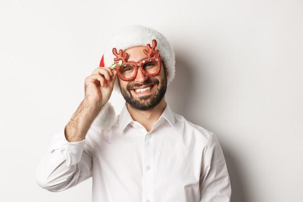 Nahaufnahme des hübschen bärtigen kerls in den weihnachtsfestgläsern und in der weihnachtsmütze, lächelnd und wünscht frohe weihnachten, stehend