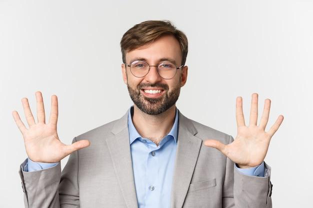 Nahaufnahme des hübschen bärtigen mannes in der brille und im grauen anzug, nummer zehn zeigend
