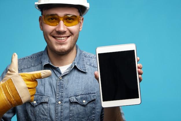 Nahaufnahme des hübschen freundlich aussehenden jungen unrasierten männlichen mechanikers oder klempners in gelben handschuhen
