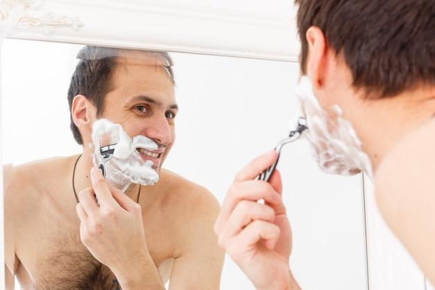 Nahaufnahme des hübschen jungen mannes, der sich im badezimmer rasiert