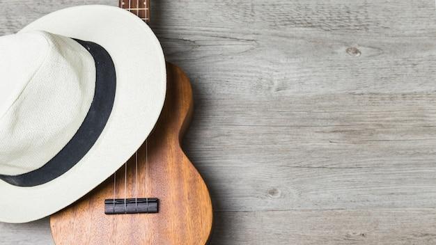Nahaufnahme des hutes über der gitarre gegen hölzernen hintergrund
