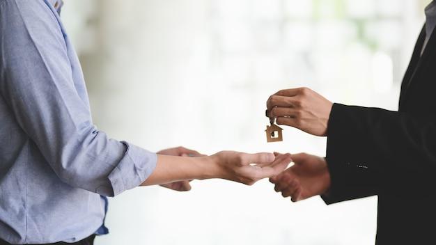 Nahaufnahme des immobilienmaklers, der seinem kunden den hausschlüssel gibt