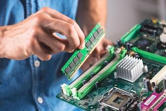 Nahaufnahme des Ingenieurs das RAM-Speichermodul in Computermotherboard setzend