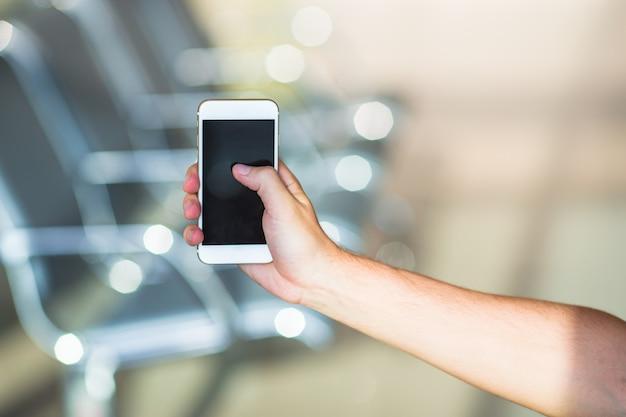 Nahaufnahme des intelligenten telefons des gebrauches des jungen mannes im flughafen nach innen