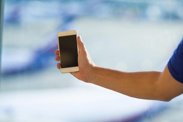 Nahaufnahme des intelligenten telefons des gebrauches des jungen mannes im flughafen