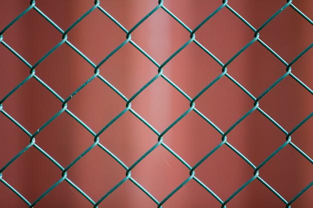 Nahaufnahme des isolierten gemalten einfachen geometrischen schwarzen eisenmetalldrahtkettengliedzauns eon dunkelrot. zaun-, schutz- und gehegekonzept.