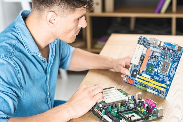 Nahaufnahme des it-mannes, der den motherboardstromkreis lernt
