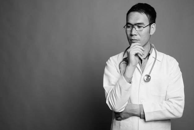 Nahaufnahme des jungen asiatischen mannarztes, der brillen trägt