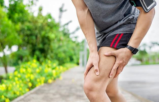 Nahaufnahme des jungen asiatischen sportmannes hat schmerzen an muskeln und gelenken während des trainings im freien, über dem trainieren oder laufen und dem sportverletzungskonzept