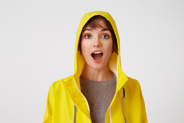 Nahaufnahme des jungen attraktiven mädchens in einem gelben regenmantel mit einem überraschten ausdruck auf ihrem gesicht, der über weißer wand mit weit geöffneter motte und augen steht. positives emotionskonzept.