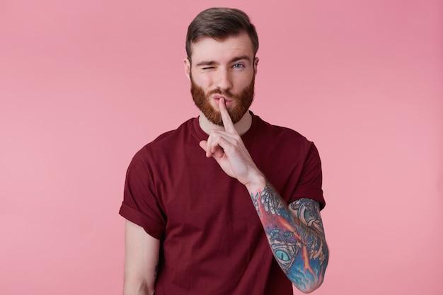 Nahaufnahme des jungen bärtigen mannes mit tätowierter hand hält vorderfinger auf den lippen, zeigt schweigeste, isoliert über rosa hintergrund mit einem mit hochgezogener augenbraue erhoben.