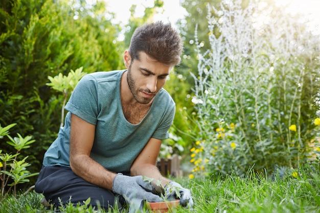 Nahaufnahme des jungen ernsthaften bärtigen mannes im blauen y-hemd und in den konzentrierten handschuhen, die im garten arbeiten und sprossen in blumentopf pflanzen. gärtner verbringt tag in seinem landhaus