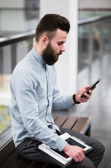 Nahaufnahme des jungen geschäftsmannes sitzend auf bank unter verwendung des handys