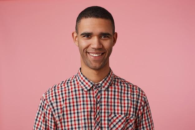 Nahaufnahme des jungen glücklichen attraktiven dunkelhäutigen kerls im karierten hemd, betrachtet die kamera mit positivem ausdruck, breit lächelnd und steht über rosa hintergrund.