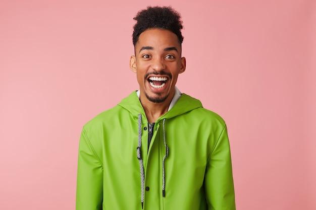 Nahaufnahme des jungen glücklichen erstaunten afroamerikanischen gutaussehenden kerls lächelt breit, schaut überrascht mit weit offenem mund, steht.