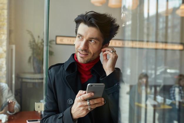 Nahaufnahme des jungen gutaussehenden dunkelhaarigen unrasierten mannes, der ohrhörer einführt, während musik hört und positiv beiseite schaut und über caféhintergrund aufwirft