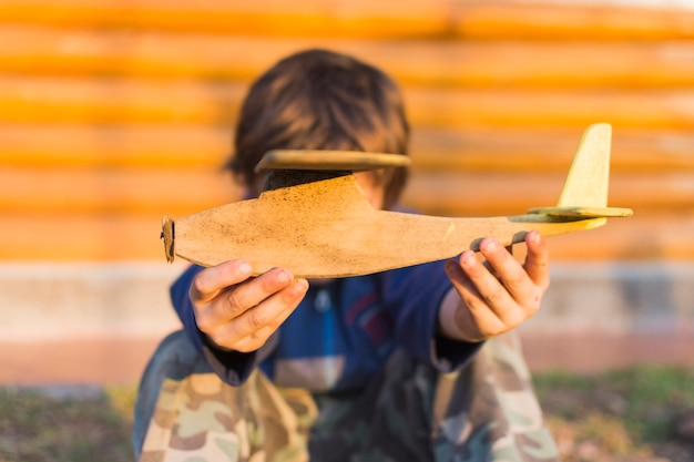 Nahaufnahme des jungen hölzernes flugzeug in seinen händen halten