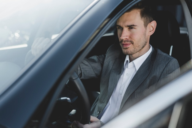 Nahaufnahme des jungen hübschen geschäftsmannes, der im autositz sitzt