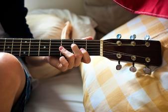 Nahaufnahme des jungen kaukasischen Jungen, der Gitarre auf Bett spielt